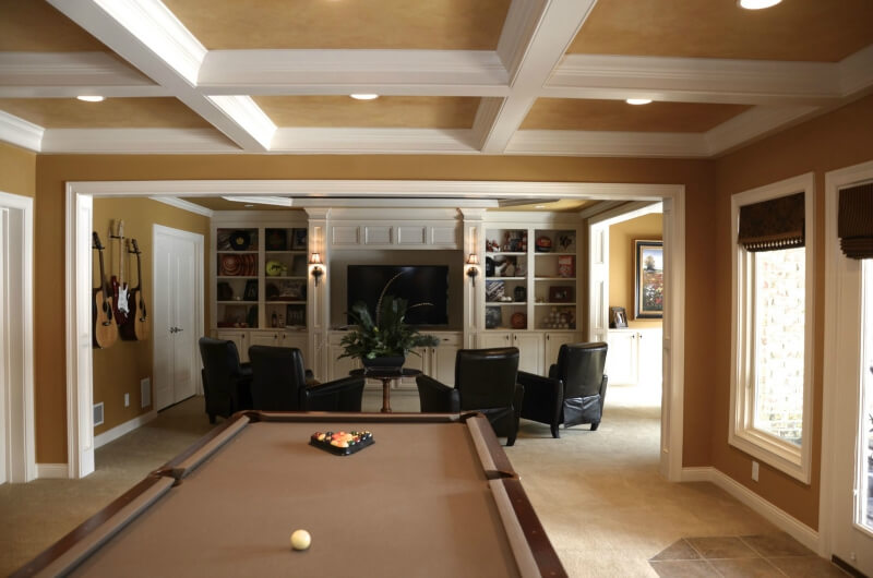 Luxurious man cave with billiards table, tile floor and entertainment area surrounded by 4 comfortable black chairs.