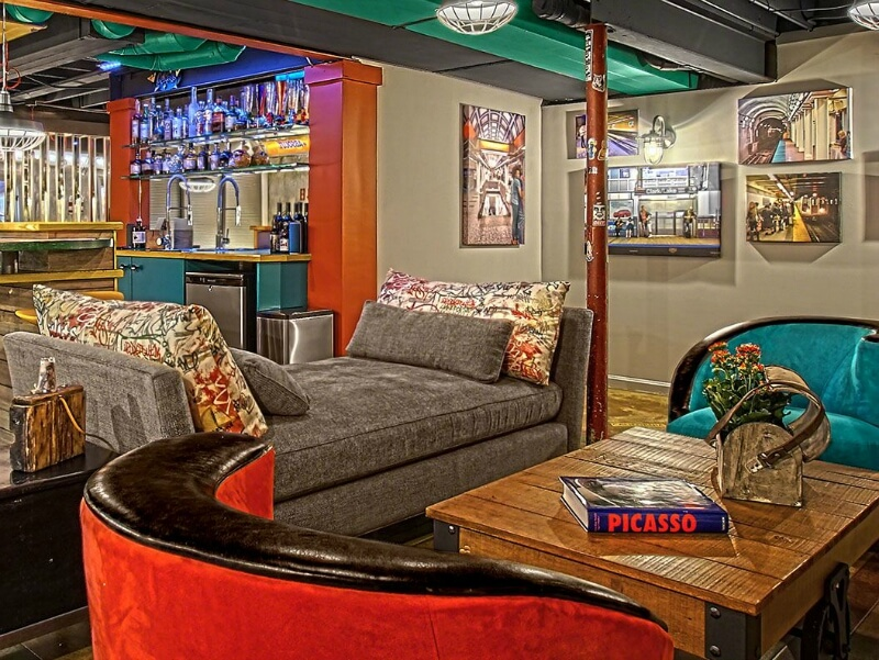 Colorful basement man cave with art on the wall, colorful bar fully stocked and colorful furniture. Exposed beams on the ceiling.