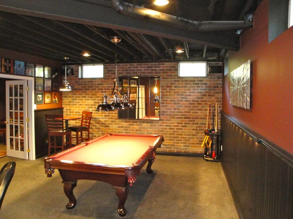 Rustic basement man cave billiards room with brick wall and exposed wood beams