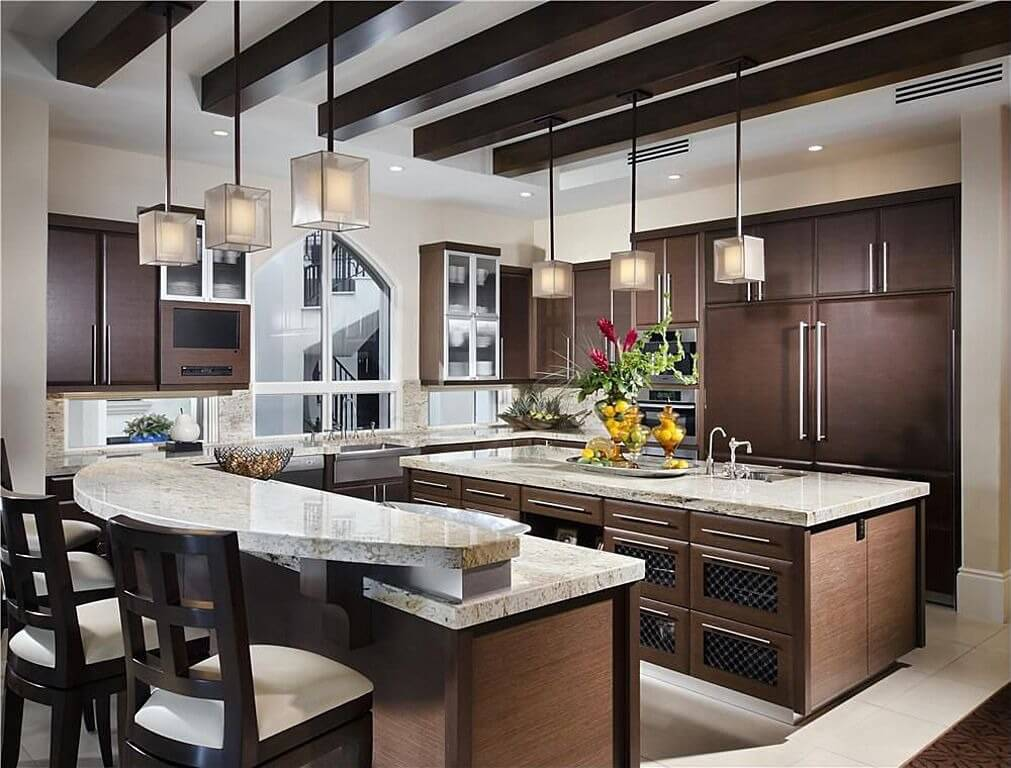 Medium sized kitchen with two islands. One island is 2 levels for an ...