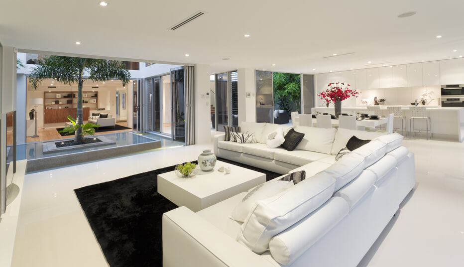Modern U-shaped home with courtyard. The all-white living room looks out onto courtyard with fountain and tree which can view other rooms of the home through floor-to-ceiling windows.