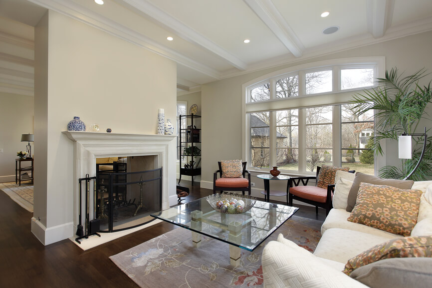 Formal living room in luxury home in white and wood design. Located just off the foyer, but separated by the large fireplace.