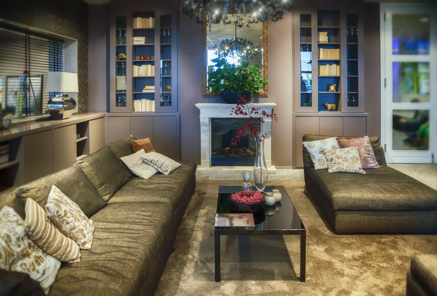 Built-in cupboards and shelving surround this living room with goldish-brown furniture and carpeting