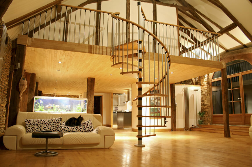 Vaulted ceiling with exposed wood beams in this open living space home with spiral staircase winding down to the living room.