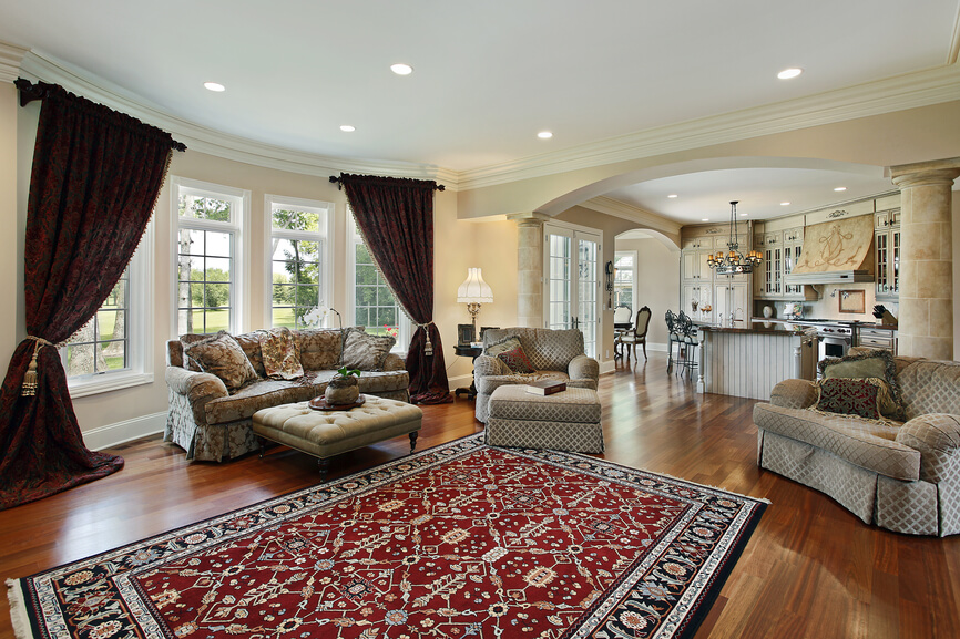 Open living space in upscale home with wood flooring throughout. Living room area has rug and casual furniture.