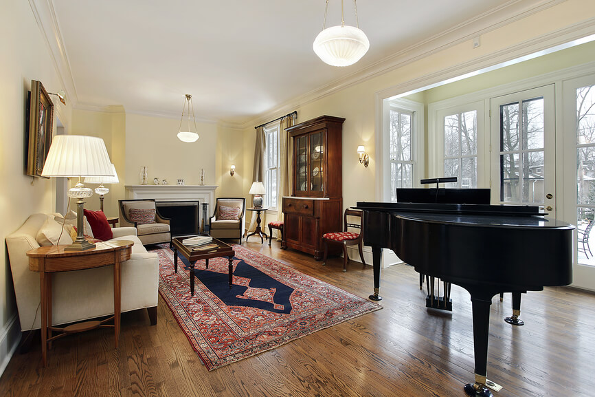 Formal living room with wood floors, rug, black baby grand piano, fireplace and glass doors leading tot he backyard.