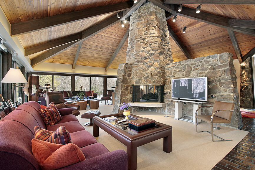 Casual living room in huge open concept living space in hexagon shaped home with vaulted exposed wood beamed ceiling. The center of the home is a large 2-story stone fireplace.
