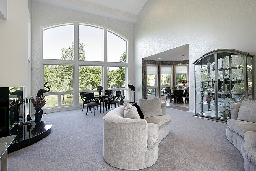 Open concept living space in modern home in all white, elevated ceiling and tall arched window.