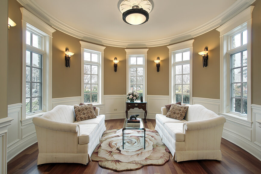 Sparsely furnished living room in oval-office like room with several windows, beige and white walls, dark wood floor and white furniture.