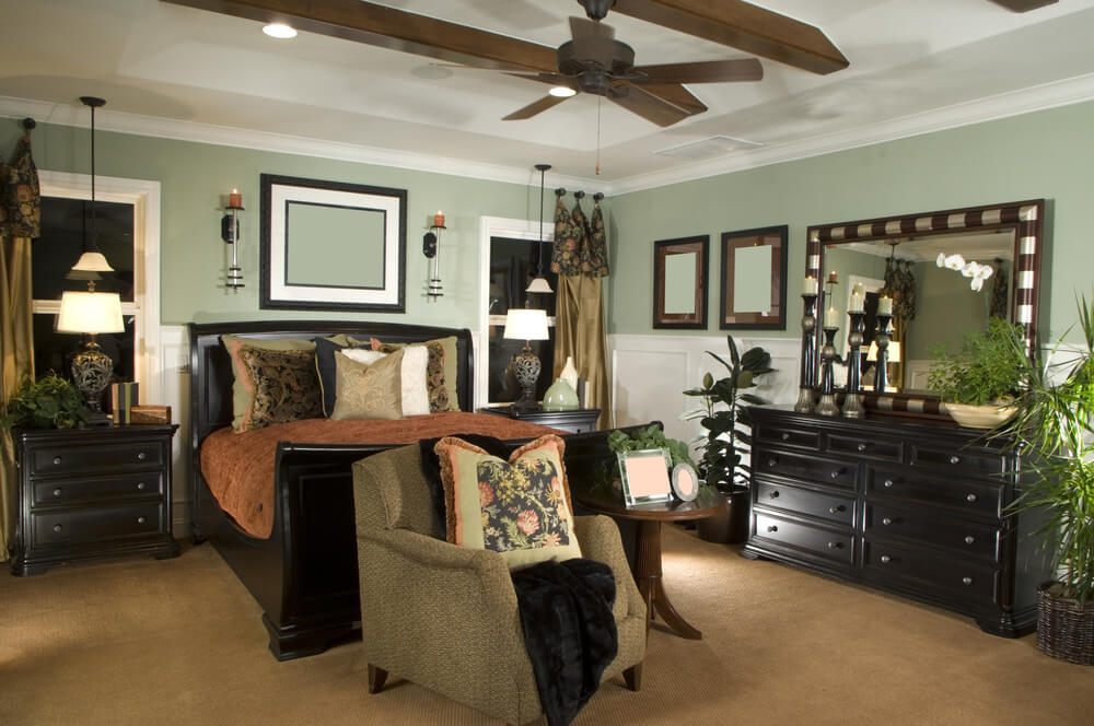 Bedroom color scheme in white, mint-green, light brown and dark brown. The mint green lightens up the otherwise dark color scheme. Large bedroom furniture give the room decorative heft. One reading chair with table creates a small reading area at the foot of the bed.