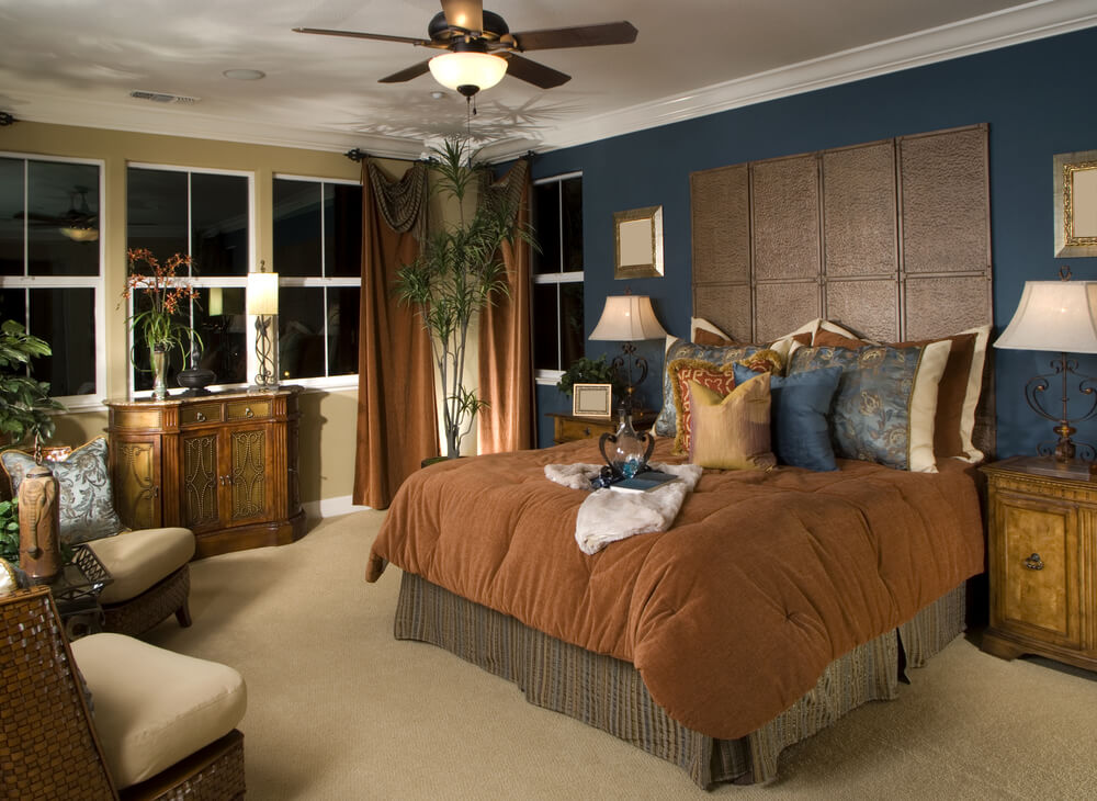 Blue wall stands out in this master bedroom design. While the room isn't large, there's a small sitting area opposite the bed. Rustic antique-looking cabinets add flair to the room.
