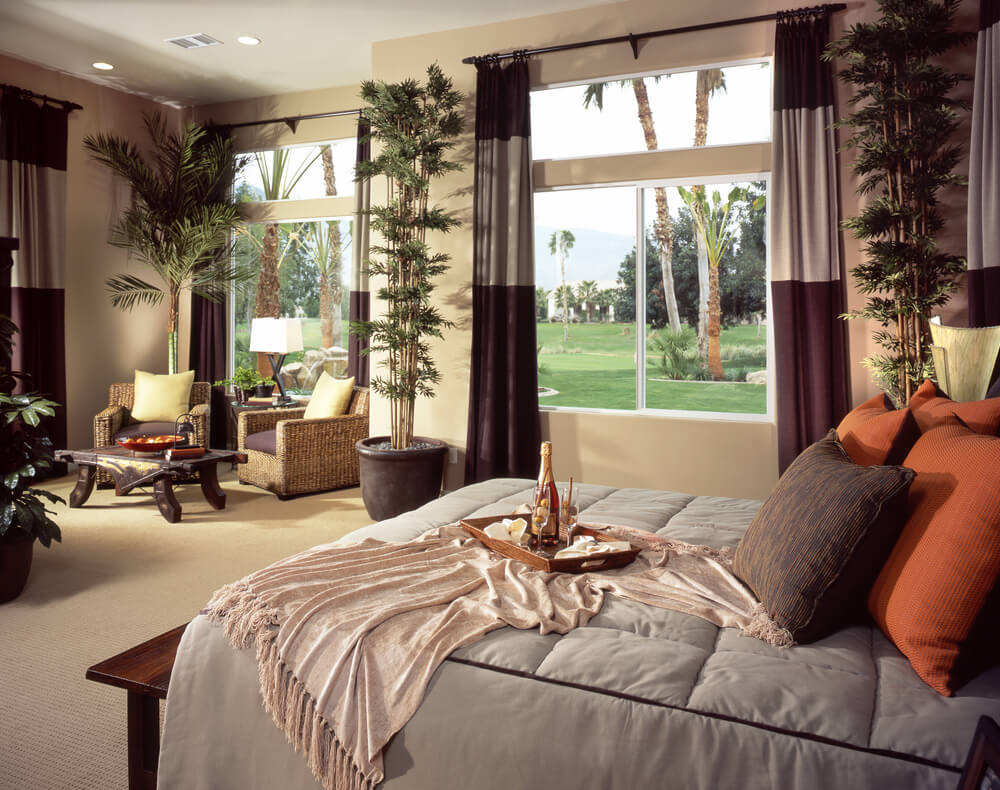 Large master bedroom with wicker furniture sitting area which includes a custom wood coffee table. Large windows look out onto the sprawling lawn with palm trees.