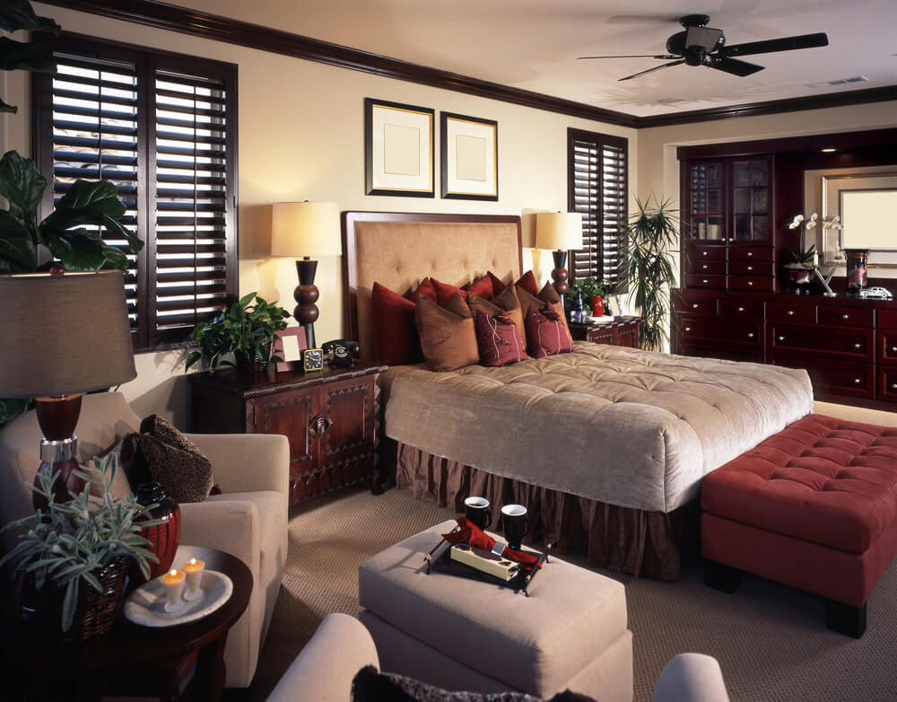 Richly decorated master bedroom with built in dark wood cabinets, large cushioned ottoman at the foot of the bed and separate sitting area in the room opposite the built-in cabinets.