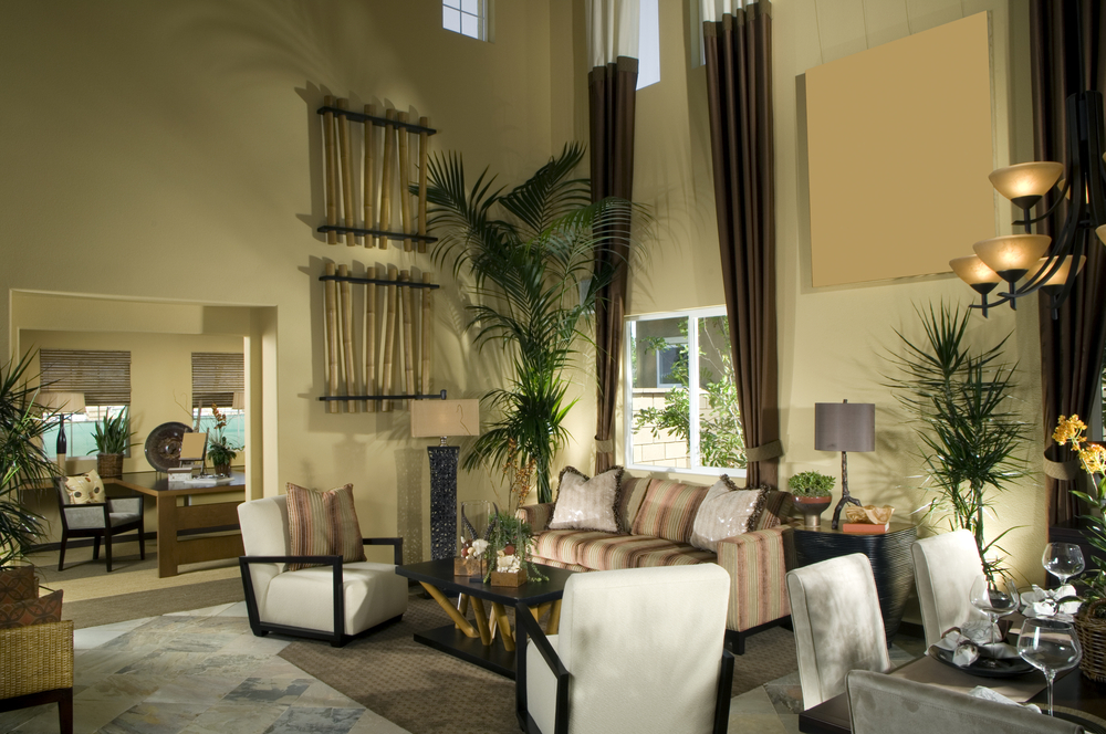 Open space living area with living room and dining room. Floor is tile with a rug and color scheme is in earth tones.