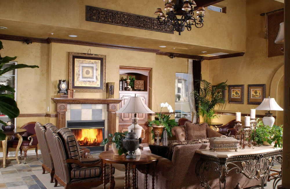 Formal living room design in large space with side card table, brown furniture in U-shape facing a fireplace
