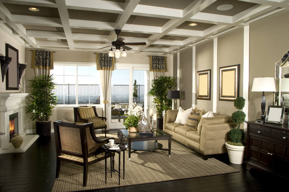Living room design with glass doors to large patio. Dark wood floor with brown rug sets the setting for the contemporary furniture, white and beige color scheme all set around a white fireplace.
