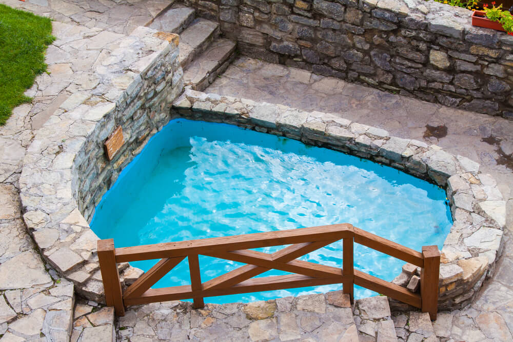 fotos jardins rusticos:Small dip pool with brick sides tucked in the corner of a yard.