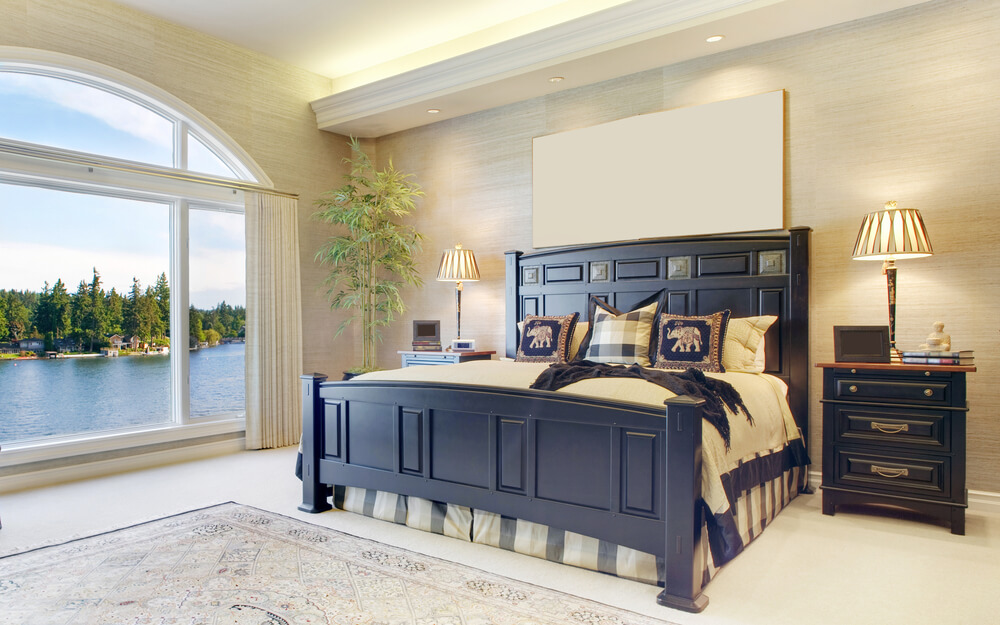 Bright airy master bedroom design with large window overlooking a lake. The star of this bedroom is the king-size bed and matching night stands.