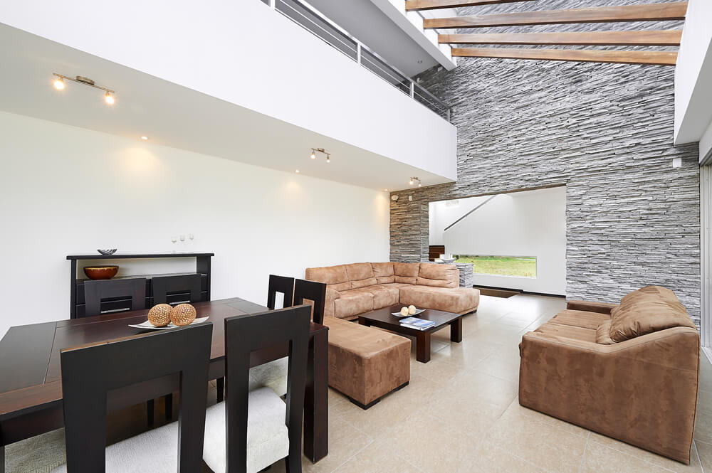 Living room in modern home design. The room has vaulted sloped ceiling with landing of second floor overlooking the living room space. Exterior wall in grey rock.