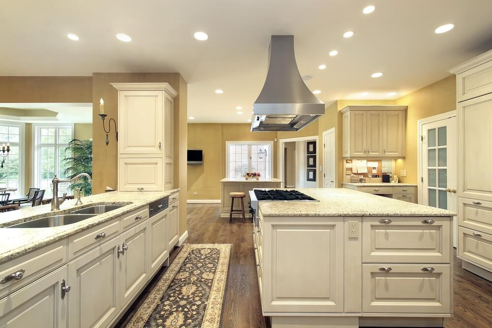 Large bright kitchen with matching island with stove for Huge kitchen designs