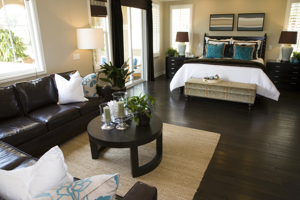 bedroom with dark brown hard flooring and furniture contrasting with