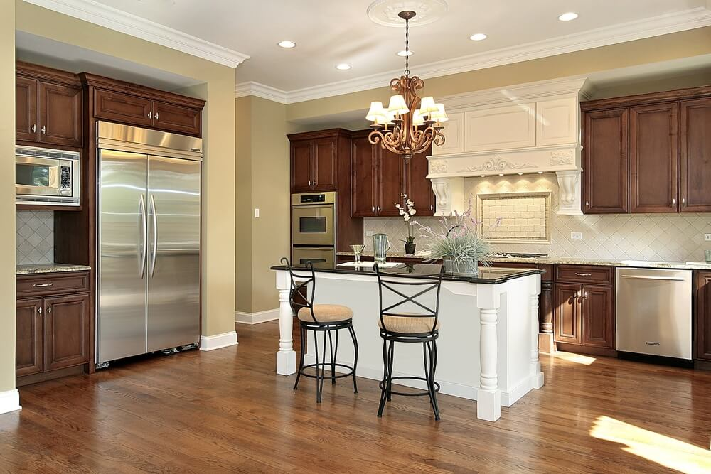 ... countertop, seated between dark wood cupboards and hardwood flooring