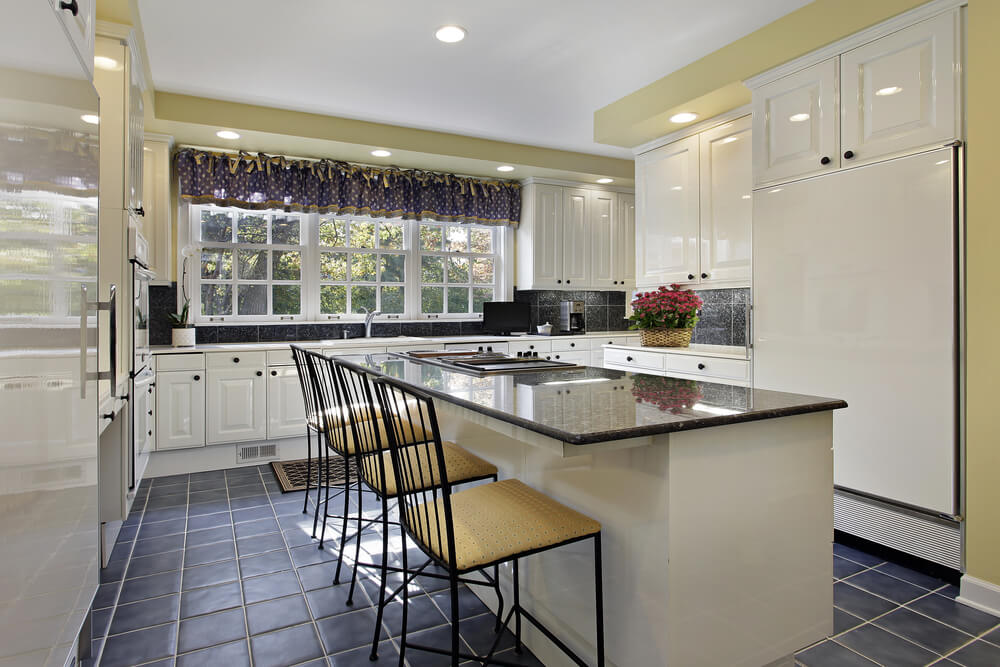 kitchen uses extensive white in contrast with dark blue tile flooring