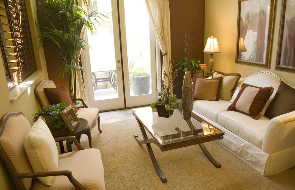 Small living room in gold brown and white color scheme with access to