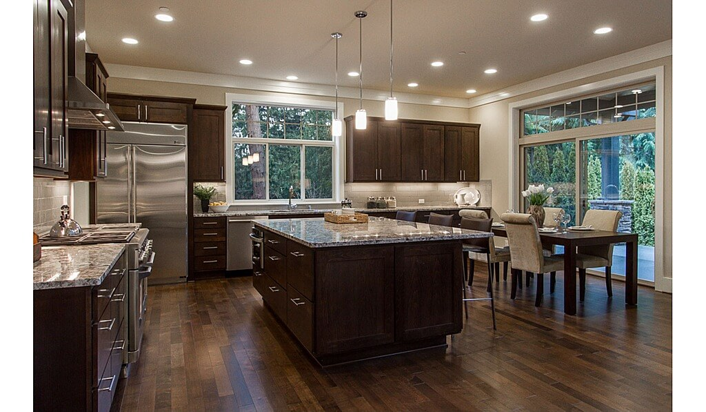 Dark wood cabinetry and flooring contrast with beige walls and brick