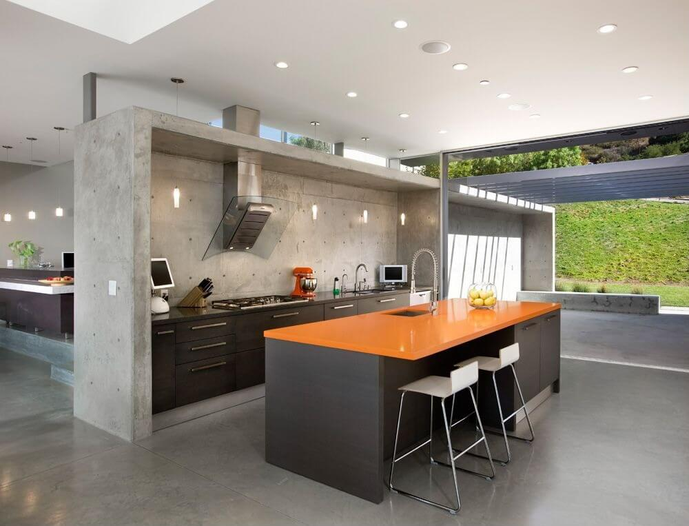 Concrete wall enclosure, black wood cabinetry and bright orange island