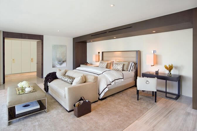 Master bedroom with loveseat at the foot of the bed