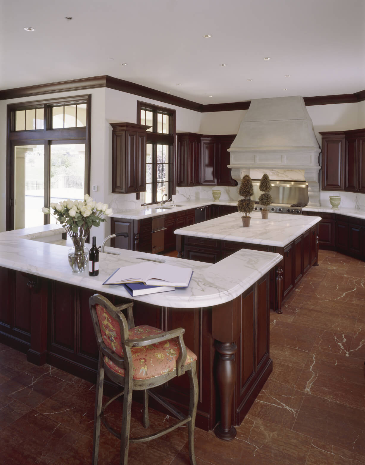 deep reddish brown marble flooring is paired with darker wood cabinetry under white marble countertops and awesome white brown wood