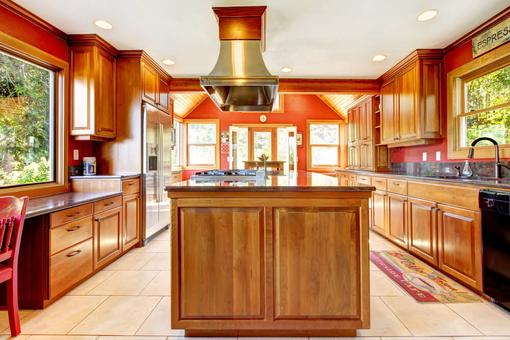 natural wood cabinets, light floor tiling, and orange wall coloring