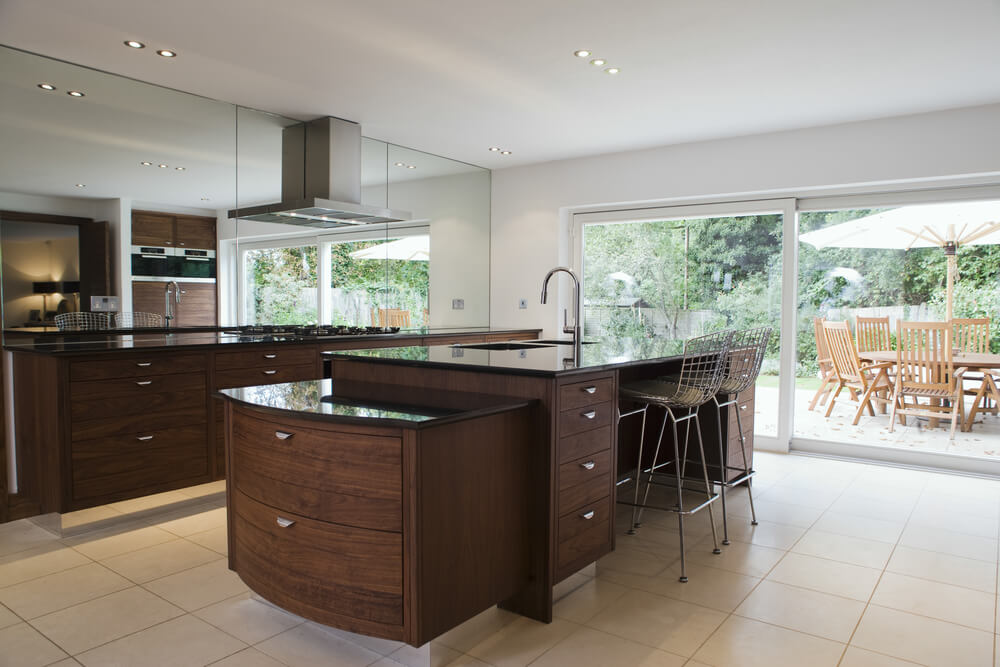 Truly unique island features prominently in this mirror-walled kitchen ...