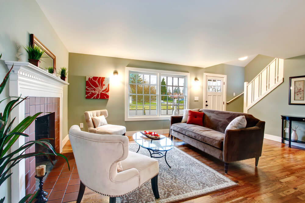 Traditional living room sits over hardwood flooring with red brick