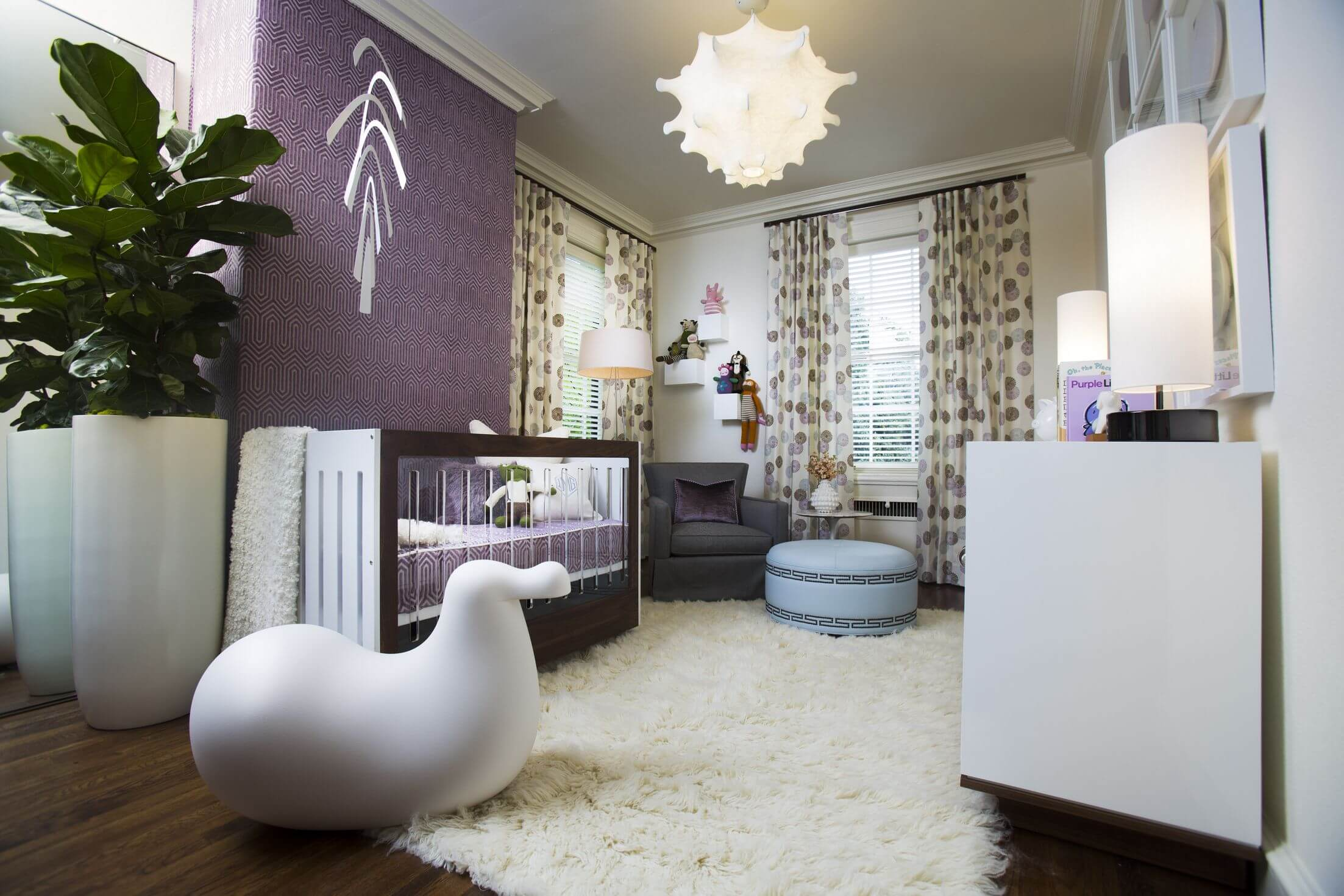 purple wall design and matching bedding accent this mostly white nursery featuring fur rug over