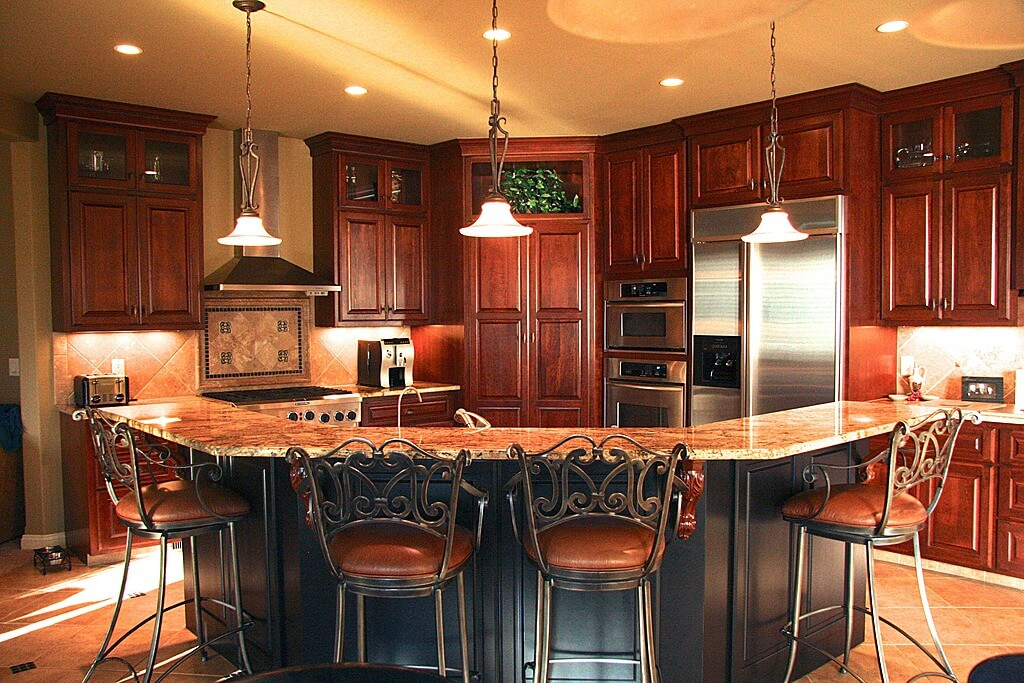Corner oriented kitchen features cherry wood cabinetry floor to ceiling, with large C-shaped ...