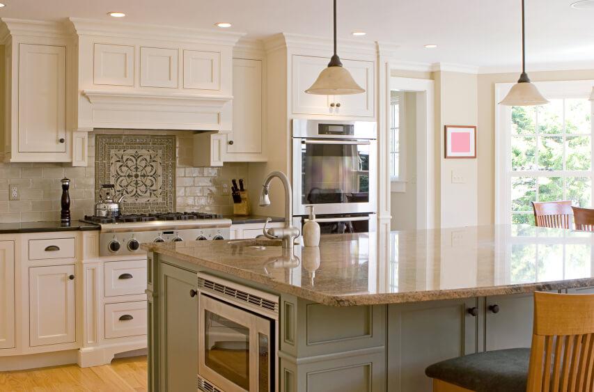 dark green island with beige marble countertop in this sunlit kitchen
