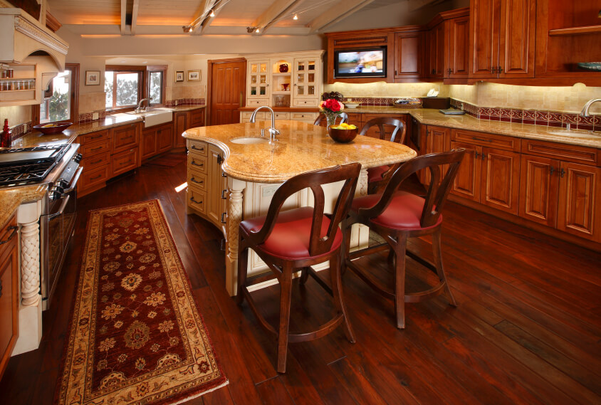 Lush cherry wood tones throughout the flooring and cabinetry of this kitchen pair with light marble countertops and curved, carved wood island in white.