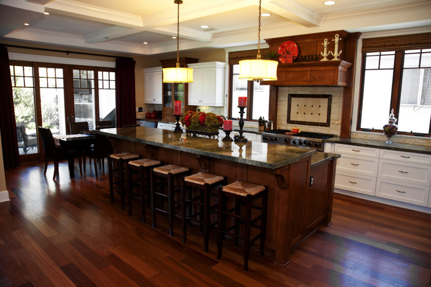 Rich dark wood tones throughout this kitchen featuring two tier island
