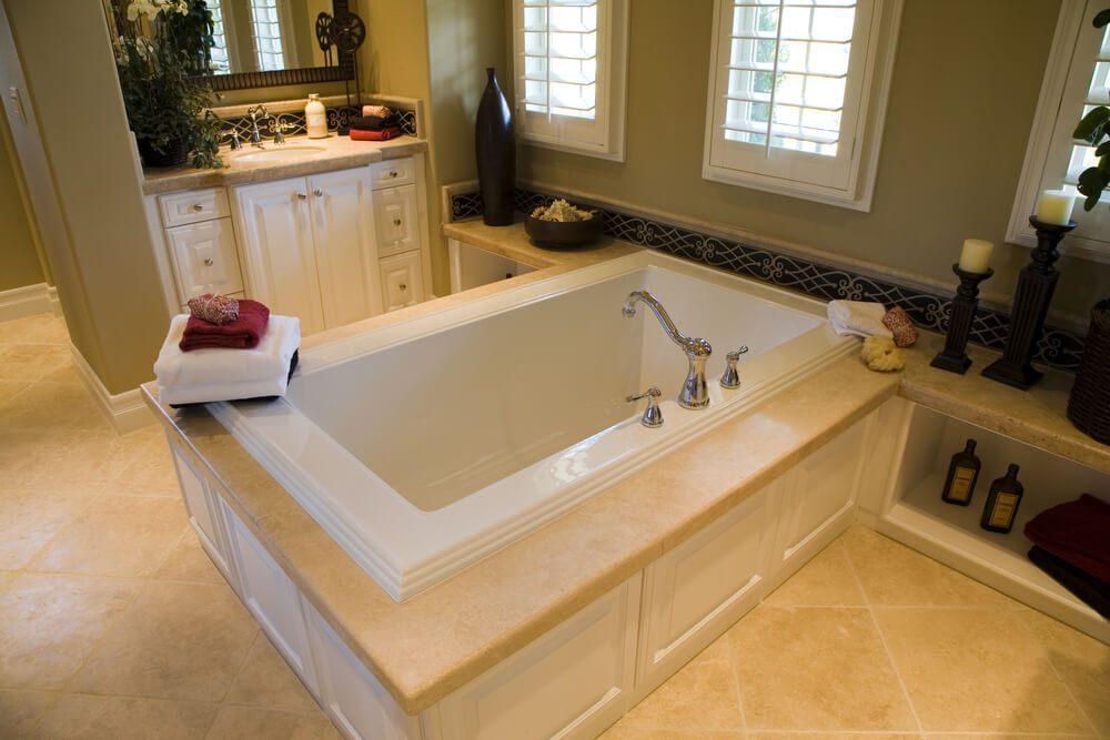 This large rectangular tub sits on white wood marble topped enclosure - 24 Luxury Master Bathroom Designs With Centered Soaking Tubs