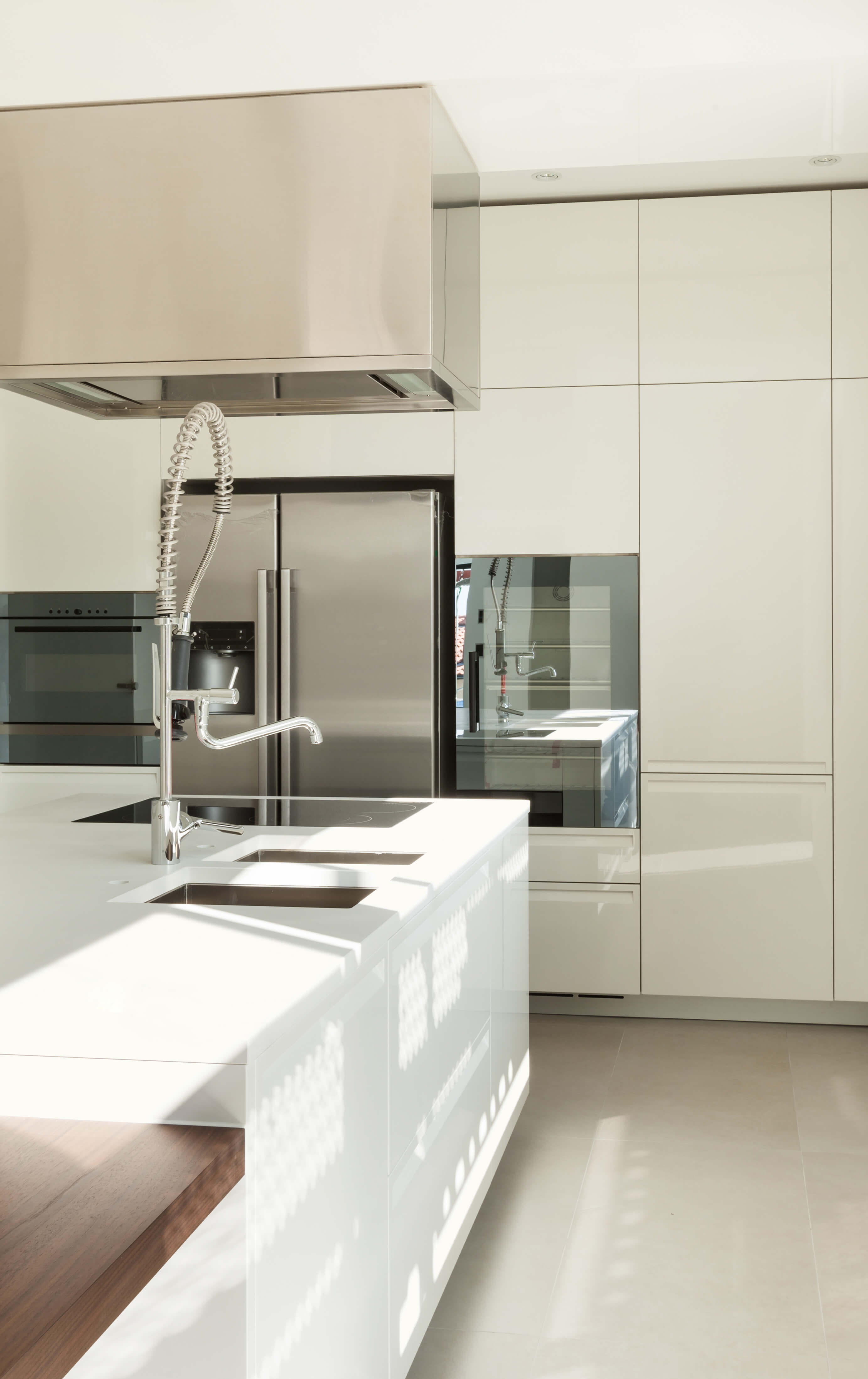 kitchen featuring glossy white cabinetry and countertops over beige