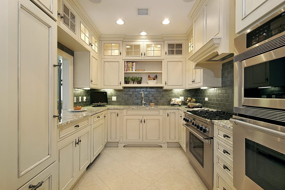 Cherry wood cabinetry and beige tile backsplash and flooring contrast