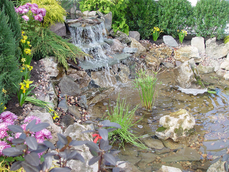 large shallow pond with a stone three tier waterfall flowing down