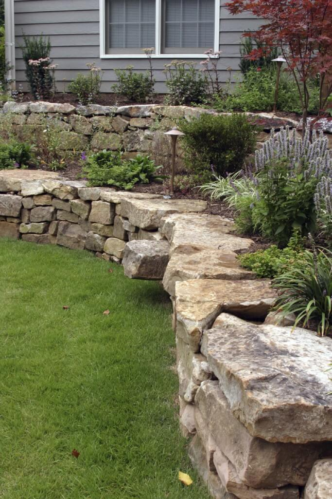 a hand laid retaining wall made out of natural stone two terraces are filled - Retaining Wall Design Ideas