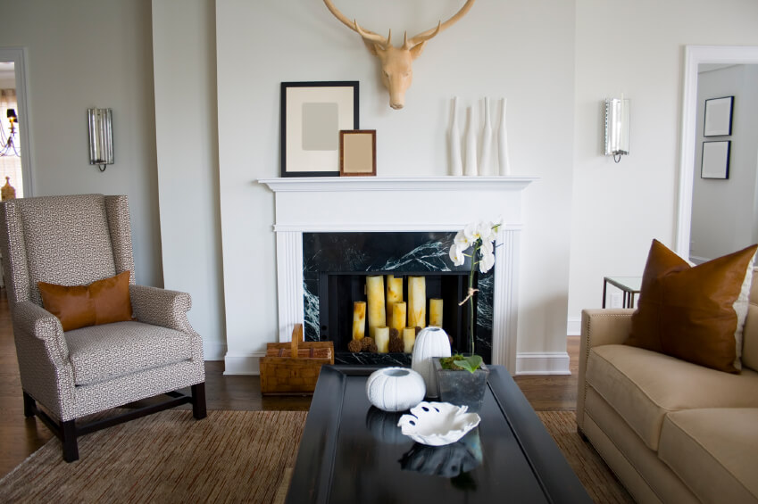 A Black Marble Fireplace Filled With Pillar Candles Dominates This Small Living Room