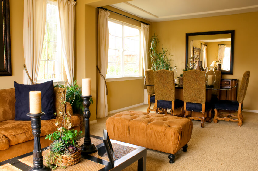 An Open Concept Living Room In Carpet With Mustard Colored Walls And Luxurious Velvet