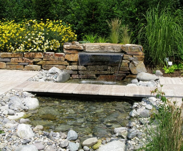 a shallow pond fed by a cascading fountain tucked into the stone edging a narrow