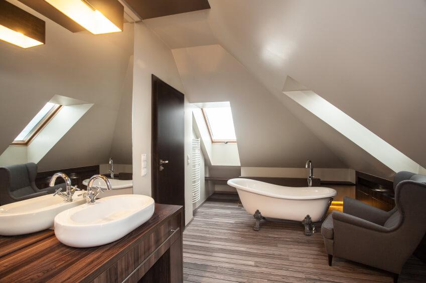 A bathroom with a clawfoot tub and a cozy armchair.