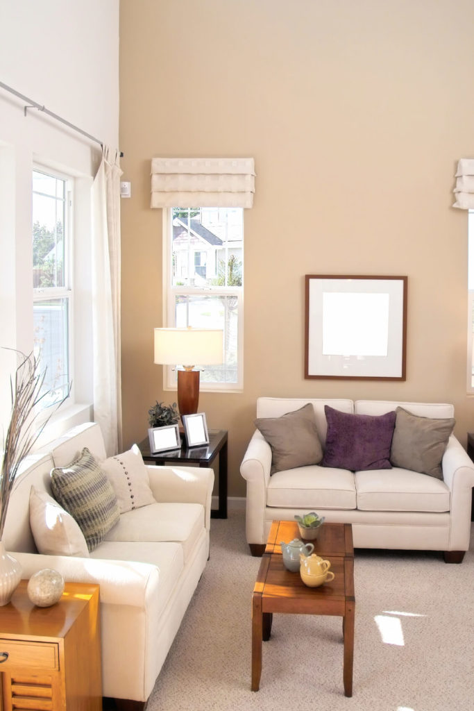 a living room in light taupe and ivory with side tables in varying shades of wood